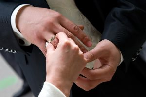 husband and wife putting wedding bands on each others hands